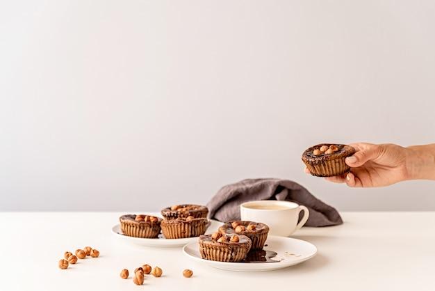 Schokoladencupcakes mit glasur, walnüssen und einer tasse kaffee