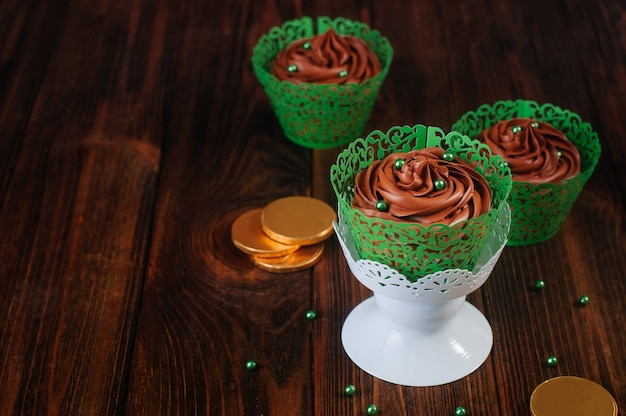 Schokoladencupcakes mit grünen zuckerstreuseln auf hölzernem hintergrund
