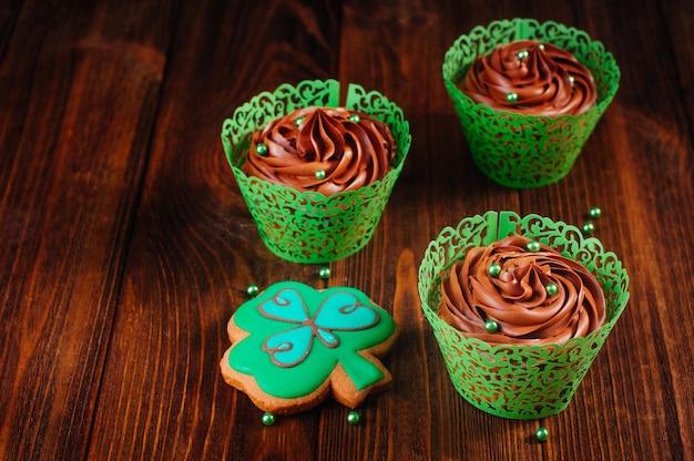 Schokoladencupcakes mit grünen zuckerstreuseln und kleekeks auf hölzernem hintergrund