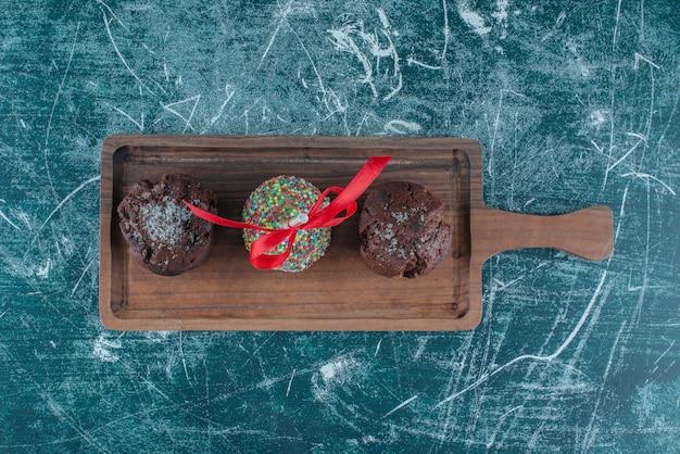 Schokoladencupcakes und ein mit süßigkeiten überzogener lutscher auf einem brett auf blauem hintergrund. hochwertiges foto