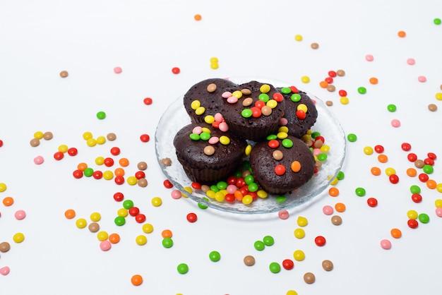 Schokoladencupcakes und eine auswahl an süßigkeiten auf einer schwarzen oberfläche