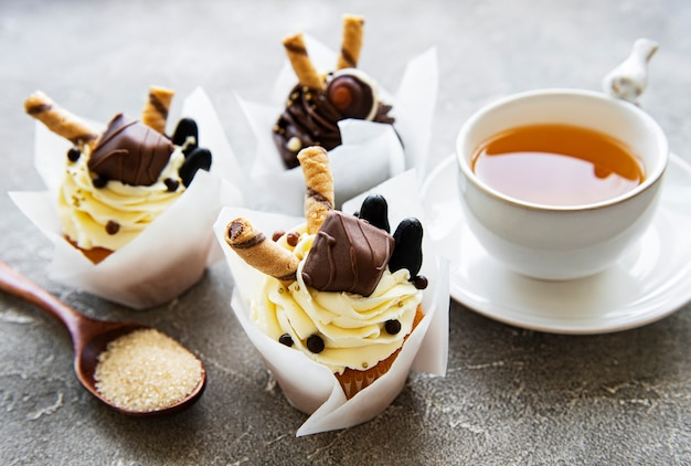 Schokoladencupcakes und eine tasse tee auf betonoberfläche