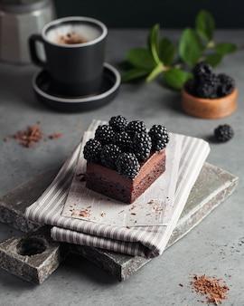 Schokoladendessert mit frischen brombeeren mit einer tasse kaffee dekoriert. dessert, rezept, coffeeshop-menü.