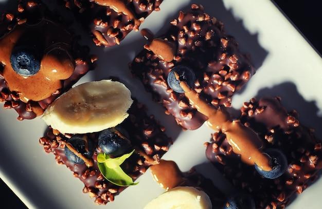 Schokoladendessert mit nüssen und frischen beeren. süßer snack für kaffeekekse in glasur und nussbrösel mit früchten.