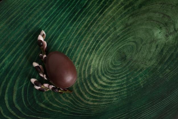 Schokoladenei und -niederlassungen auf einem grünen hintergrund mit copyspace. ansicht von oben