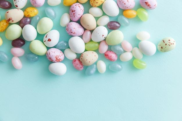 Schokoladeneier der ostersüßigkeit und geleebonbons lokalisiert auf blauem tisch