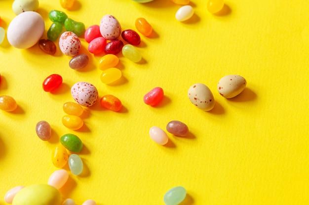 Schokoladeneier der ostersüßigkeit und geleebonbons lokalisiert auf trendigem gelbem tisch