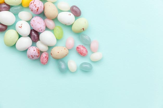 Schokoladeneier der ostersüßigkeit und geleebonbons lokalisiert auf trendigem pastellblau.