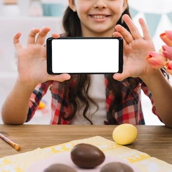 Schokoladeneier vor einem mädchen, das weiße bildschirmanzeige des handys zeigt