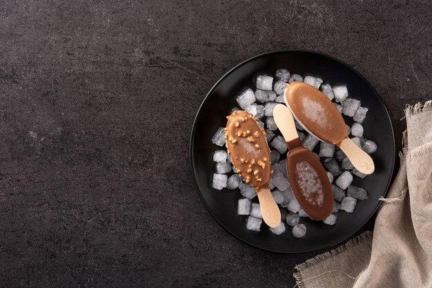 Schokoladeneis am stiel und crushed ice auf schwarzem tisch