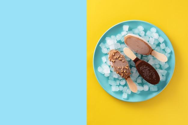 Schokoladeneis am stiel und zerstoßenes eis auf blauem teller auf gelbem und blauem tisch