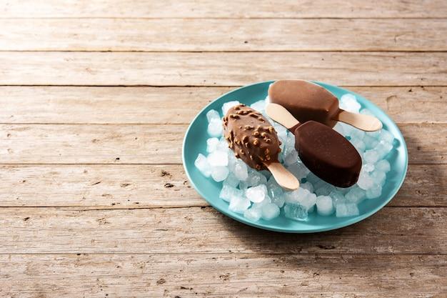 Schokoladeneis am stiel und zerstoßenes eis auf blauem teller auf holztisch