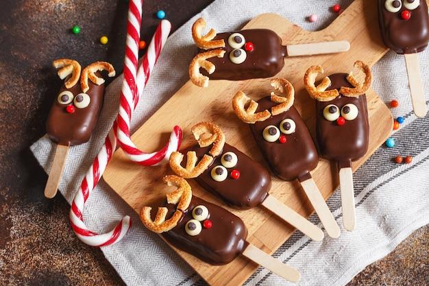 Schokoladeneis auf einem stock mit einem weihnachtshirschgesicht mit bonbonroter nase