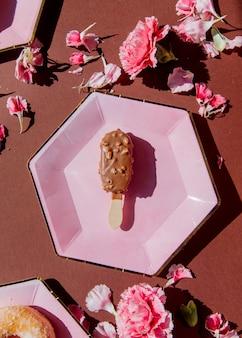 Schokoladeneis auf tellern mit dianthusblättern auf braunem hintergrund