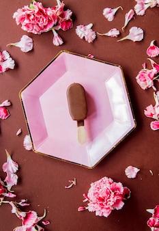 Schokoladeneis auf tellern mit dianthusblättern auf brauner oberfläche