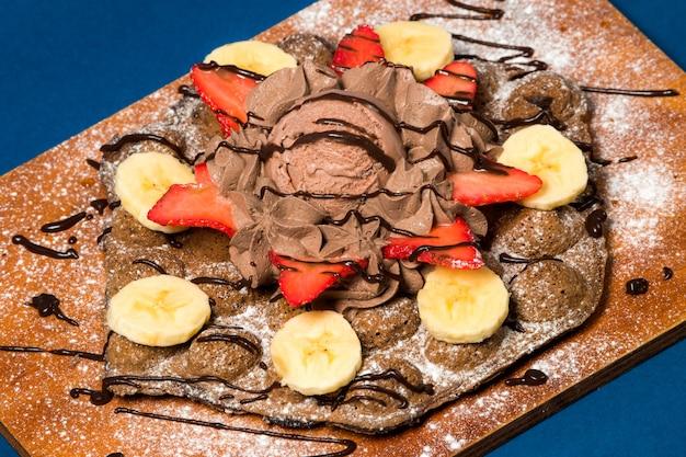 Schokoladeneis mit früchten auf holzbrett