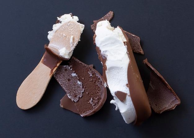 Schokoladeneis mit gebrochenem holzstabschrott auf schwarzer wand