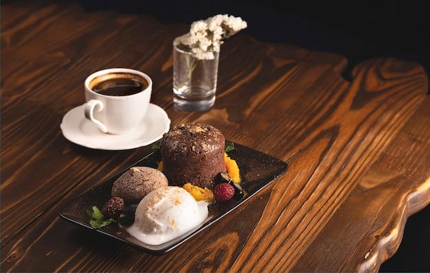 Schokoladenfondant mit eis und beeren auf einem hölzernen restauranttisch neben einer tasse kaffee
