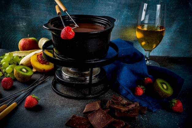 Schokoladenfondue im traditionellen fonduetopf mit gabeln, weißwein, verschiedenen beeren und früchten
