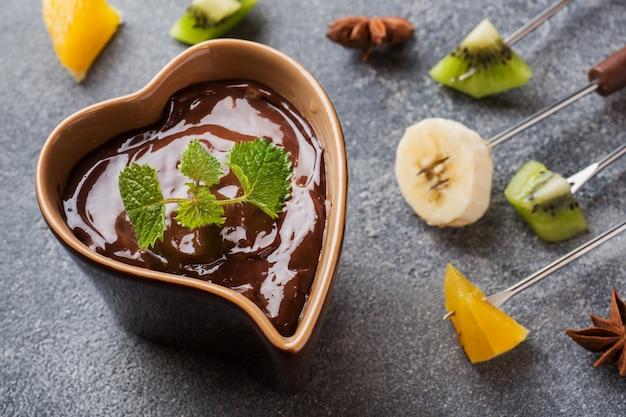 Schokoladenfondue mit früchten auf dunklem beton