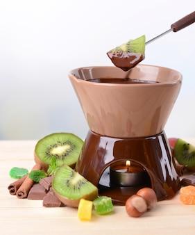 Schokoladenfondue mit früchten, auf holztisch auf grau