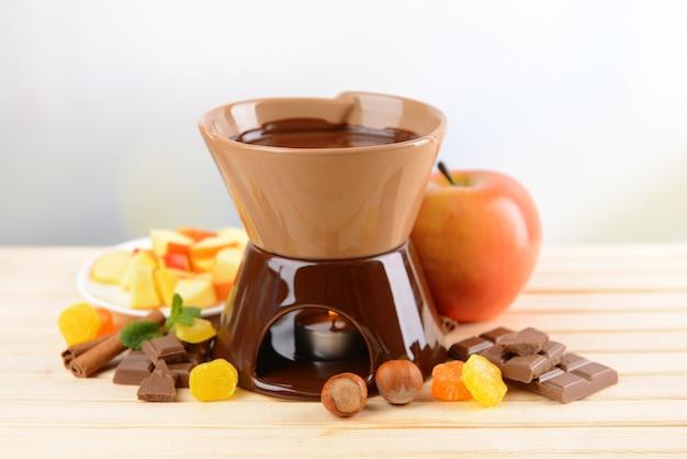 Schokoladenfondue mit früchten, auf holztisch, auf hellem hintergrund