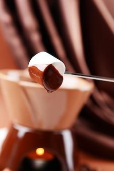 Schokoladenfondue mit marshmallow-bonbons auf brauner oberfläche
