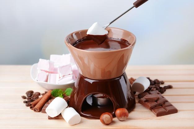 Schokoladenfondue mit marshmallow-bonbons auf holztisch
