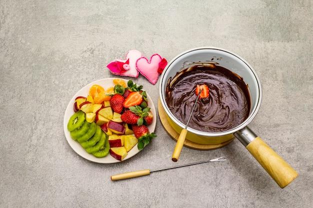 Schokoladenfondue. verschiedene frische früchte, zwei schokoladensorten, filzherzen. zutaten für ein süßes romantisches dessert.