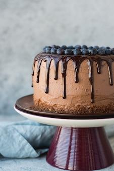 Schokoladengeburtstagstorte mit blaubeeren und schokoladenglasur auf hellem hintergrund