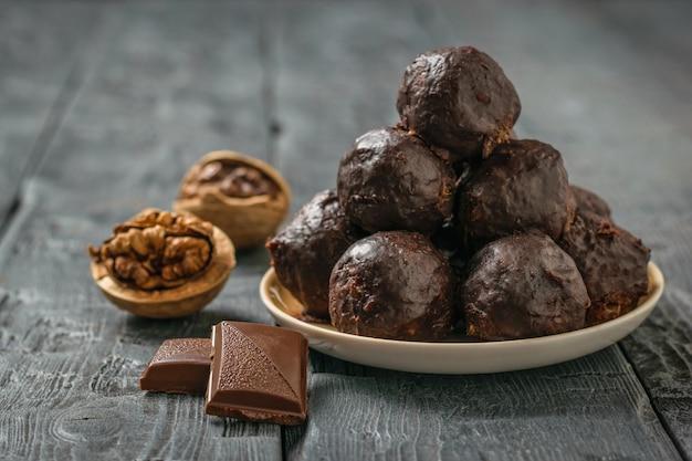 Schokoladengetränkte kugeln aus geriebenen nüssen und getrockneten früchten in einer schüssel auf einem holztisch. leckere frische hausgemachte süßigkeiten.