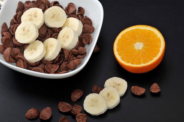 Schokoladengetreide mit bananen und halber orange