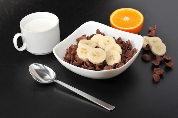 Schokoladengetreide mit bananen und orangensaft und kaffee
