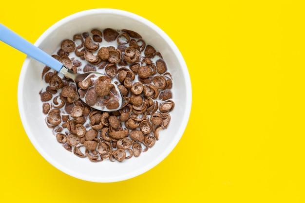 Schokoladengetreide mit milch auf gelbem hintergrund.