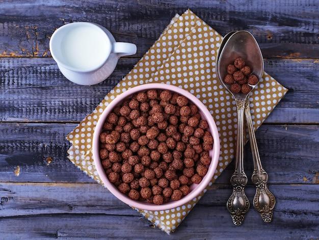 Schokoladengetreidebälle in der schüssel und in der milch