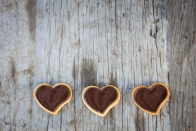 Schokoladenherz auf hölzernem hintergrund für geschenk in der valentinstagliebe.