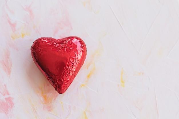 Schokoladenherz in der roten folie auf einem rosa hintergrund