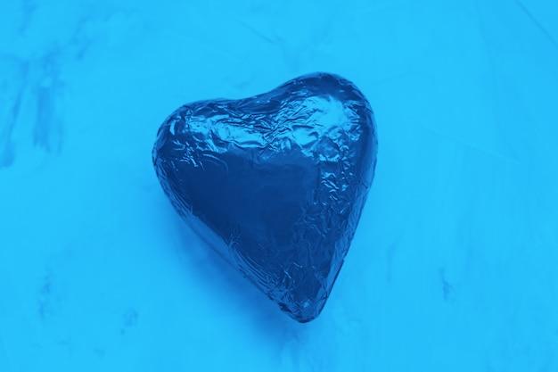 Schokoladenherz in folie. valentinstagkonzept, kopienraum, farbe des jahres