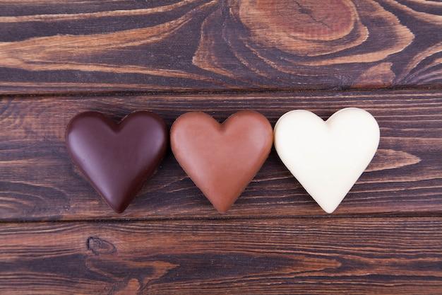 Schokoladenherzen auf einem dunklen hintergrund, nahaufnahme. internationaler schokoladentag, postkarte