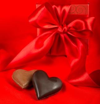Schokoladenherzen und geschenkbox mit band auf roter seidenoberfläche