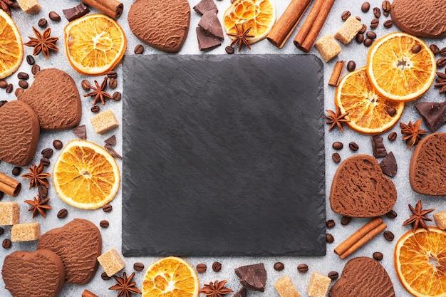 Schokoladenherzplätzchen, orangenzimt und würzige gewürze auf einem grauen tisch, draufsicht, kopienraum.