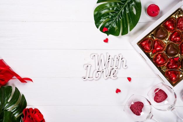 Schokoladenherzsüßigkeiten und -rotrose auf hölzernem weißem hintergrund mit kopienraum