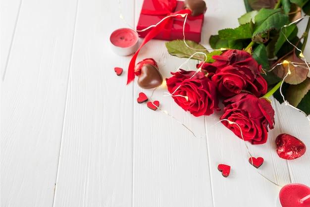 Schokoladenherzsüßigkeiten und rotrose
