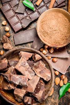 Schokoladenhintergrund. schokolade mit kakaopulver und zimt. auf einem hölzernen hintergrund.