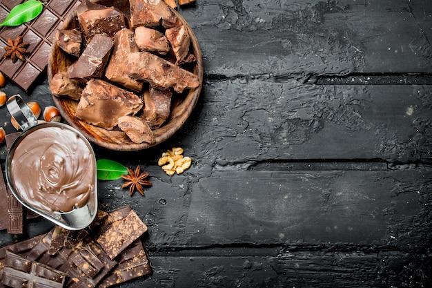 Schokoladenhintergrund. verschiedene schokoladensortimente mit paste. auf schwarzem rustikalem hintergrund.