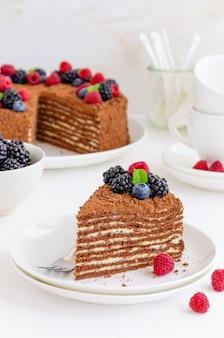 Schokoladenhonigkuchen mit sahne und frischen beeren.