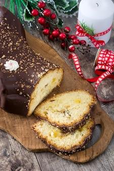 Schokoladenjulblock-weihnachtskuchen und -verzierungen auf hölzernem