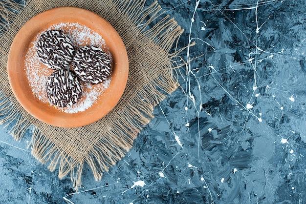 Schokoladenkeks auf einem tonteller auf der textur, auf dem blauen tisch.