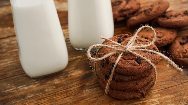 Schokoladenkeks mit milch auf holztisch. hausgemachte kekse. das konzept der natürlichen und gesunden ernährung. bäckereiprodukte