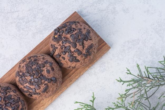 Schokoladenkeksbällchen auf einem brett neben tannenzweig, auf dem marmortisch.
